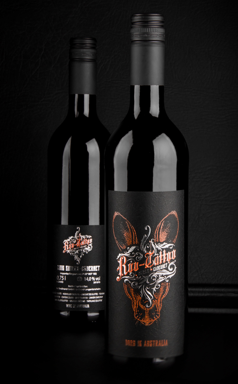 Product shot of two wine bottles standing next to each other in front of a black background. One further front showing the frontlabel and another more in the back presenting the back label.