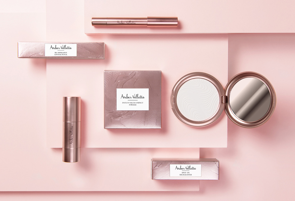 Topview of Amber Valletta makeup products for Douglas laying on a light rose background
